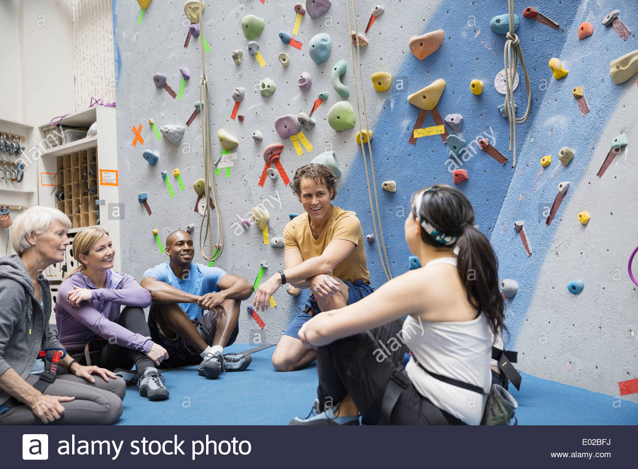 Instructor and group talking below rock climbing wall - Stock Image