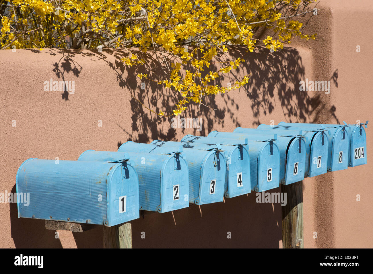 Row of blue mailboxes numbered 1 through 8 and 204. - Stock Image