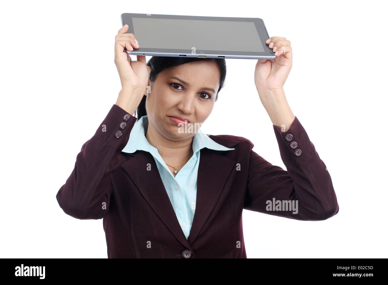Angry businesswoman throwing her tablet computer - Stock Image