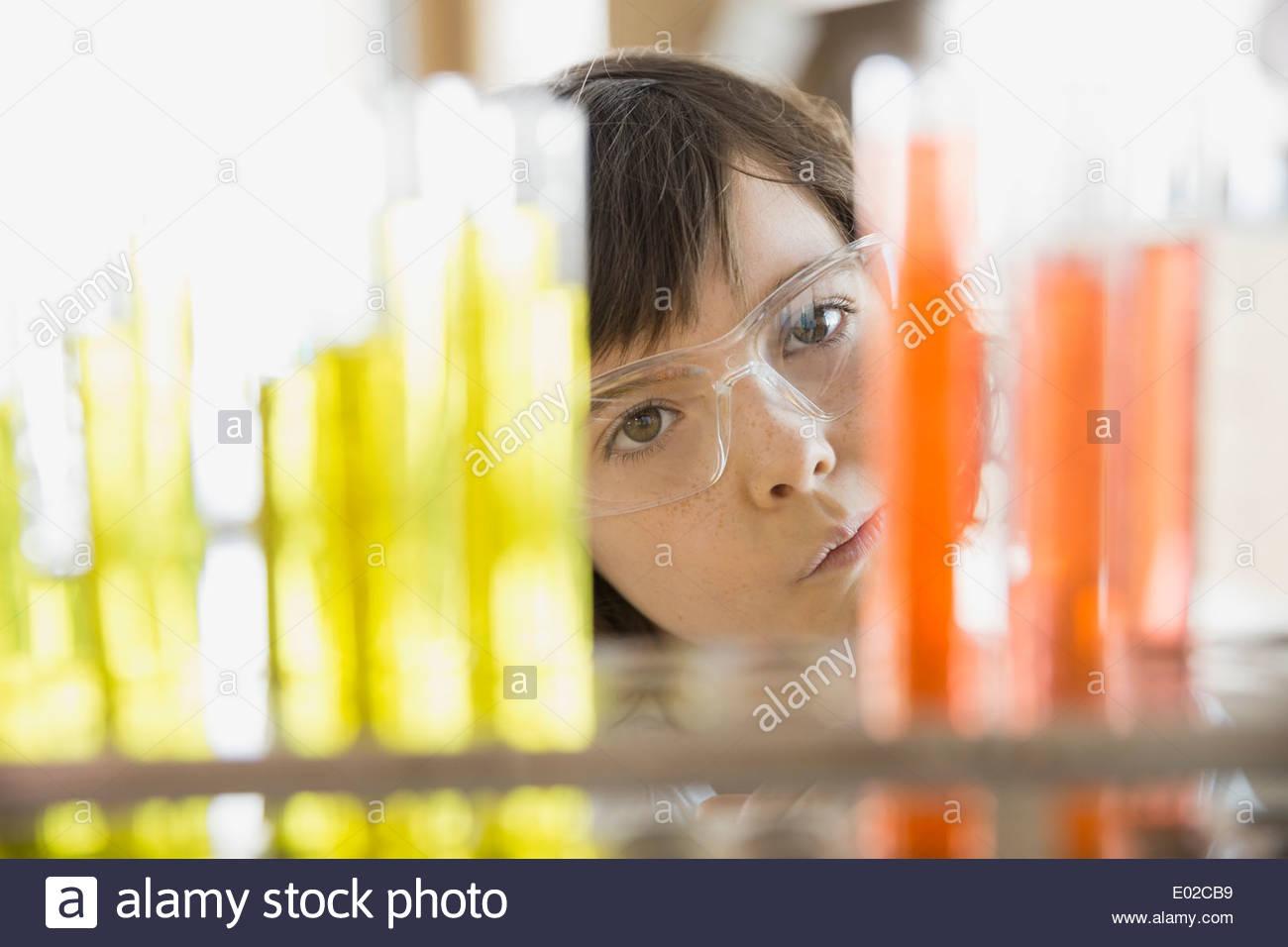 School girl looking at vials in science classroom - Stock Image