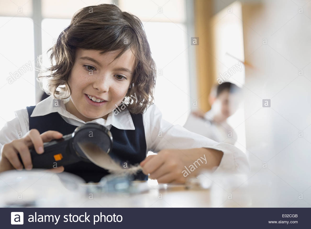 School girl conducting scientific experiment in classroom - Stock Image