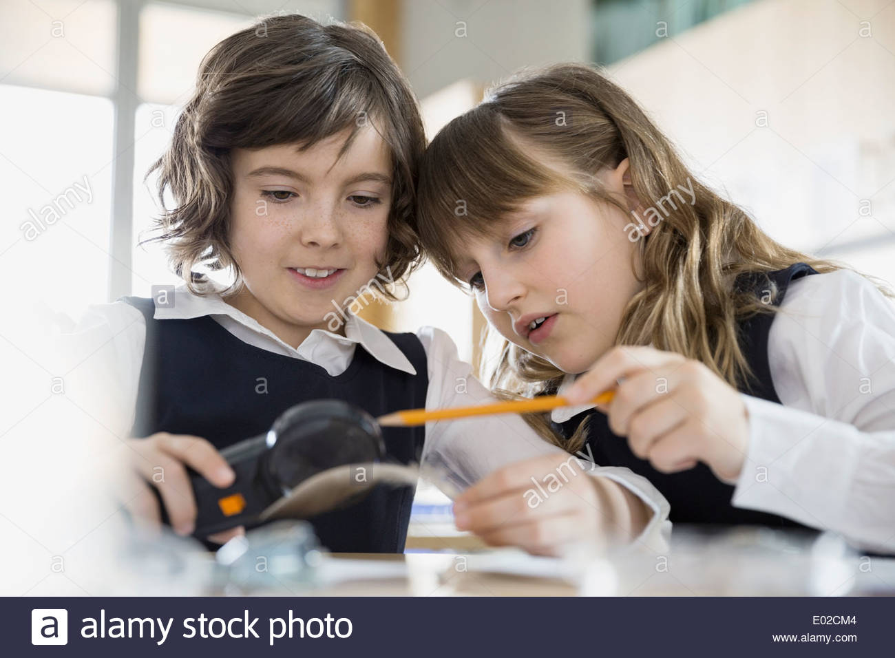 School girls conducting scientific experiment in classroom - Stock Image