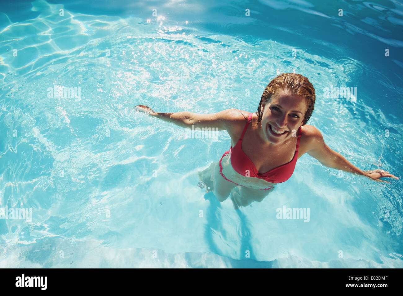 Happy young girl relaxing in a swimming pool. Smiling young woman wearing swimwear standing in pool looking at camera. Stock Photo