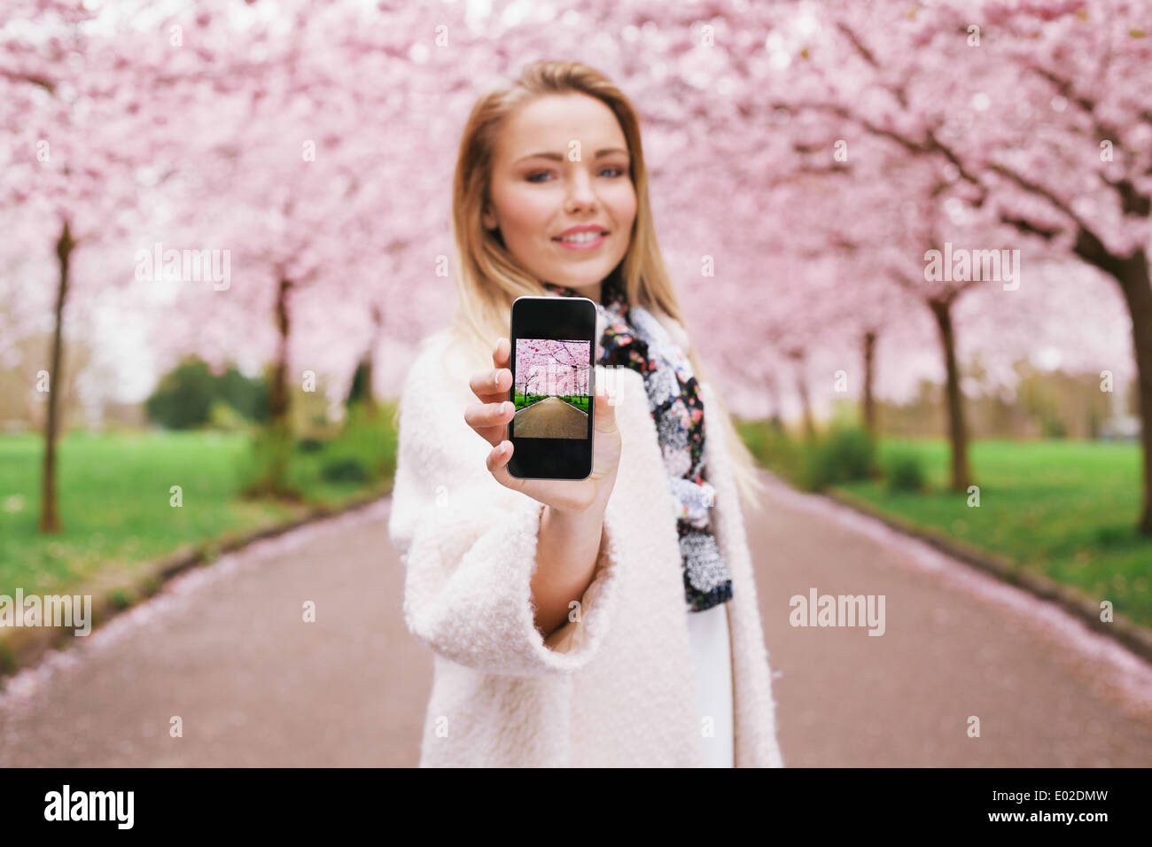Pretty young woman showing picture of spring blossom garden while standing at a park. Caucasian young female showing Stock Photo