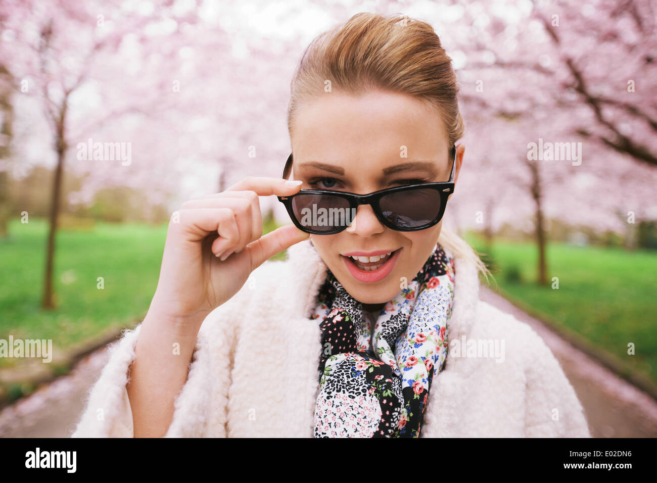 Close up image of cute young woman winking at camera. Naughty female model at spring park wearing sunglasses. Stock Photo