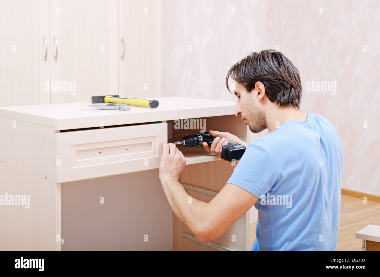 the repairer in assembly of furniture collects new furniture - Stock Image