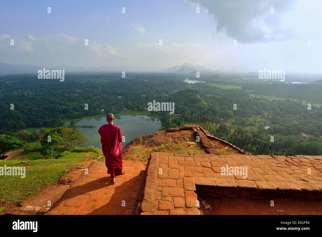 Buddhist nun enjoying the view from the ruins of the fortress on the Lion Rock, Sigiriya, UNESCO World Heritage Site, Sigiriya - Stock Image