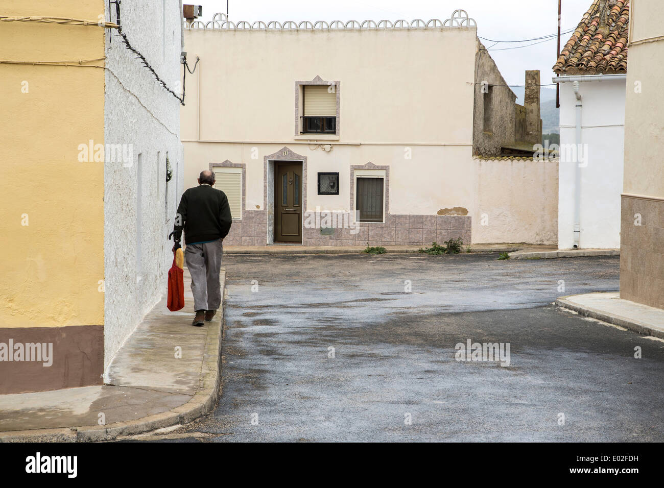Passerby walking down a street, La Portera, Province of Valencia, Spain - Stock Image