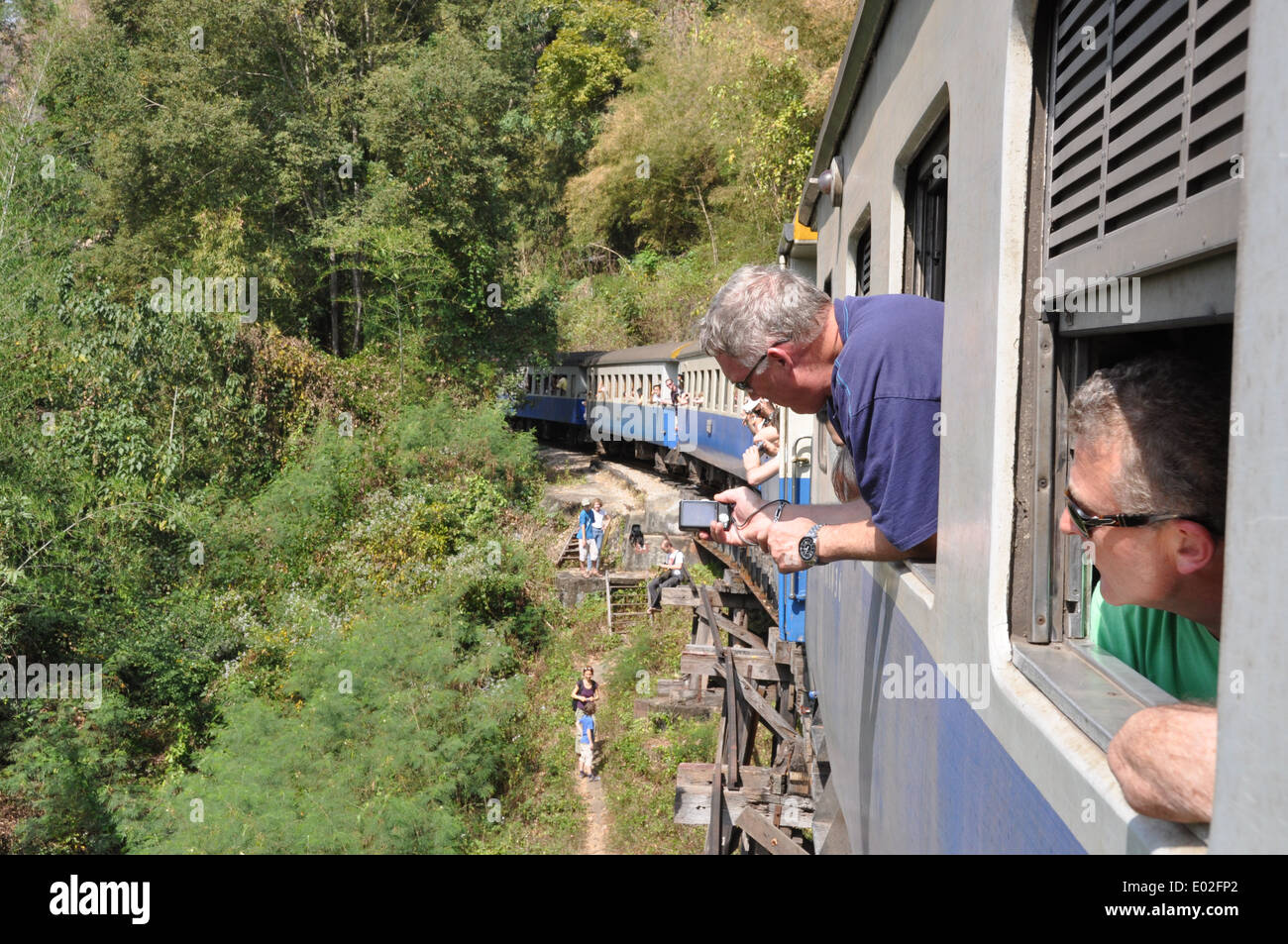 Tourists leaning out of the windows of a train on the Thai - Burma Railway, Thailand. - Stock Image