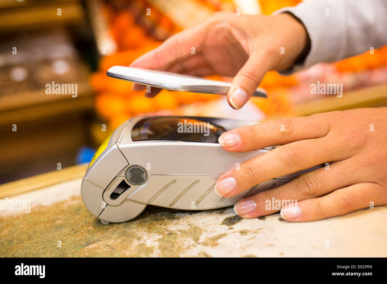 Female electronic payment close-up cell phone hand shop electronic reader - Stock Image