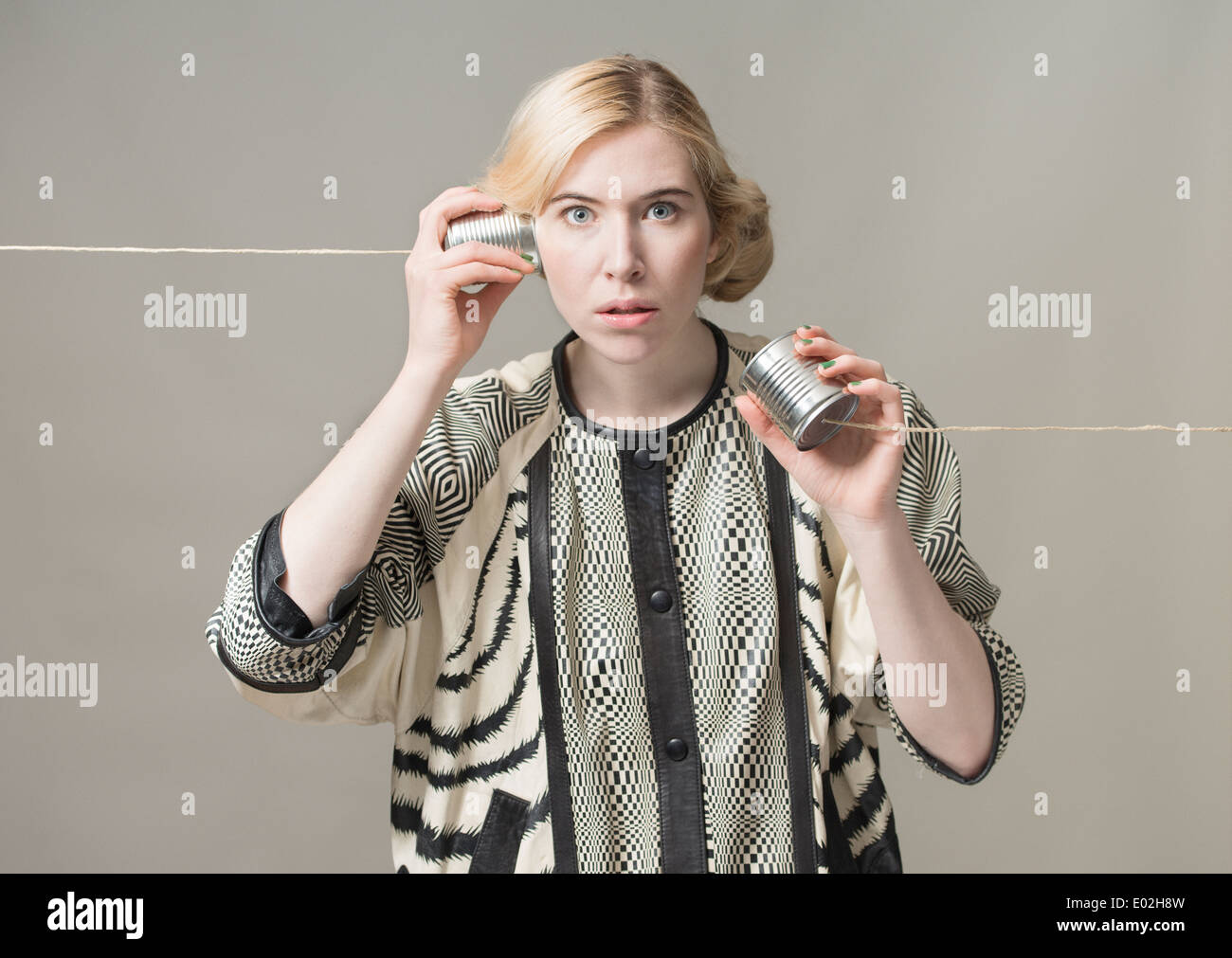 Blonde woman using tin can phone. Conceptual image of connection and communication. - Stock Image