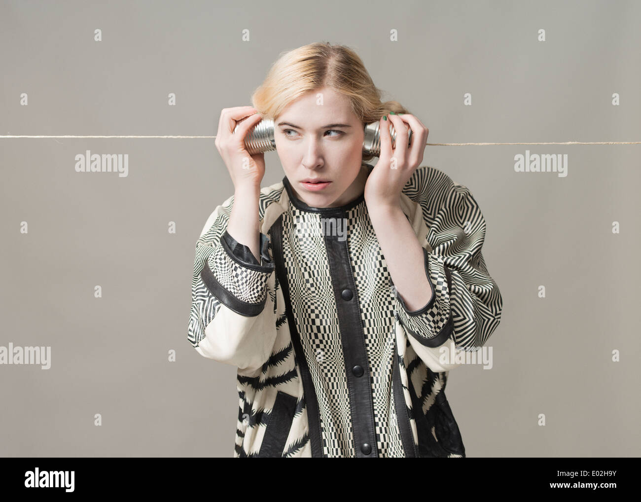 Blonde woman listening with tin can phone. Conceptual image of spying, surveillance and communication. - Stock Image