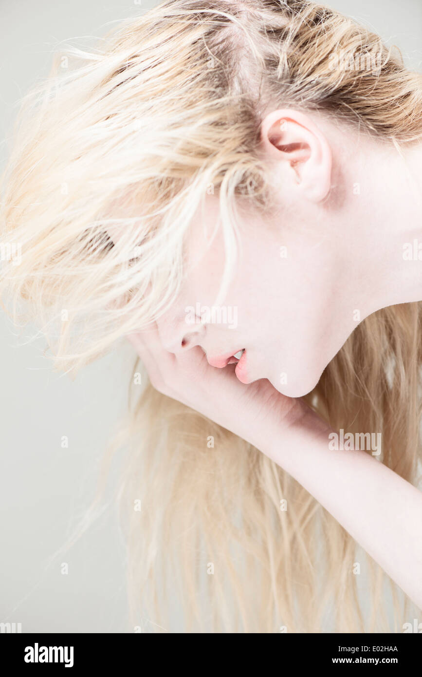 Side view of young beautiful blonde woman with long hair. Looking down, covering face with hand. - Stock Image