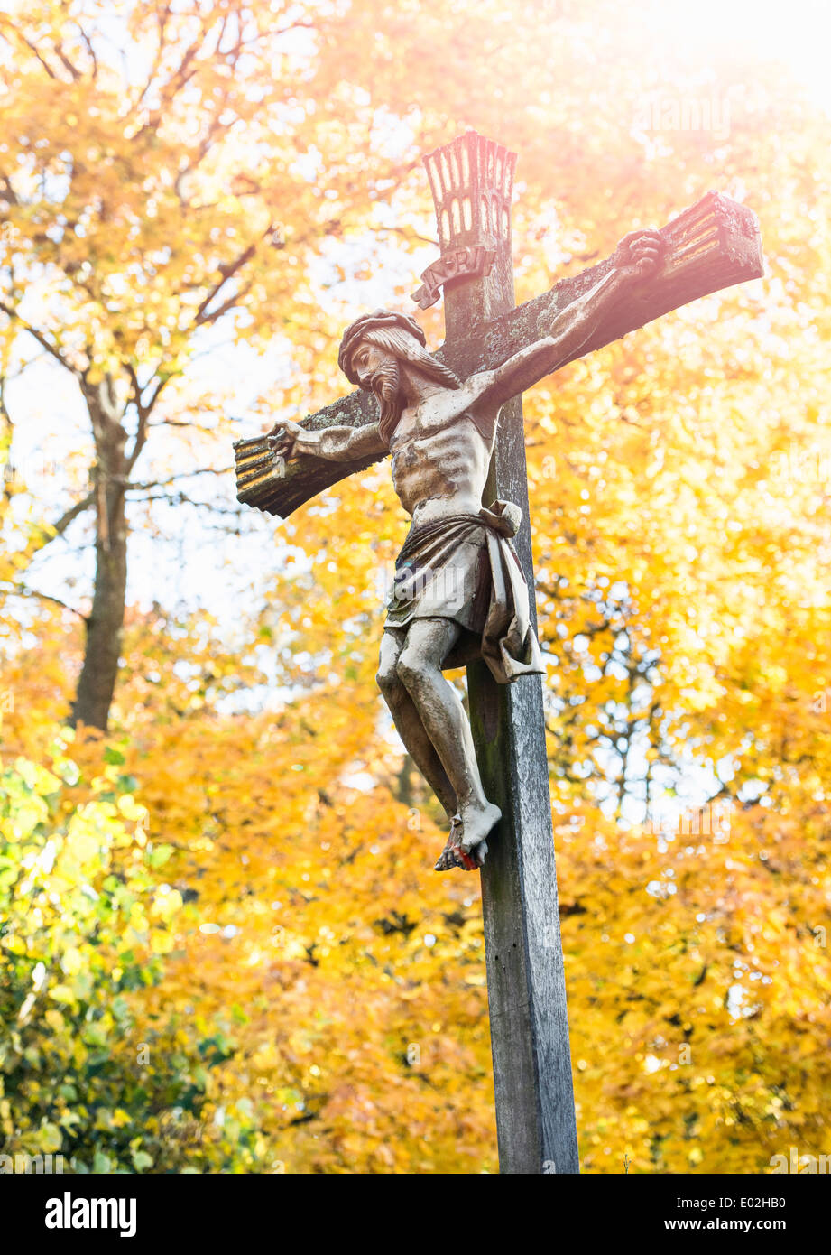 Jesus Christ on the cross with fall trees in the background. Cemetery in Stockholm, Sweden. - Stock Image