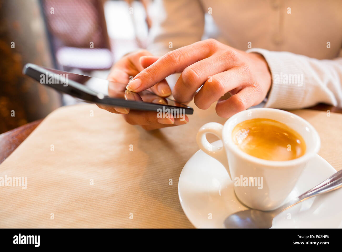 Female smart phone coffee bar sms mail - Stock Image