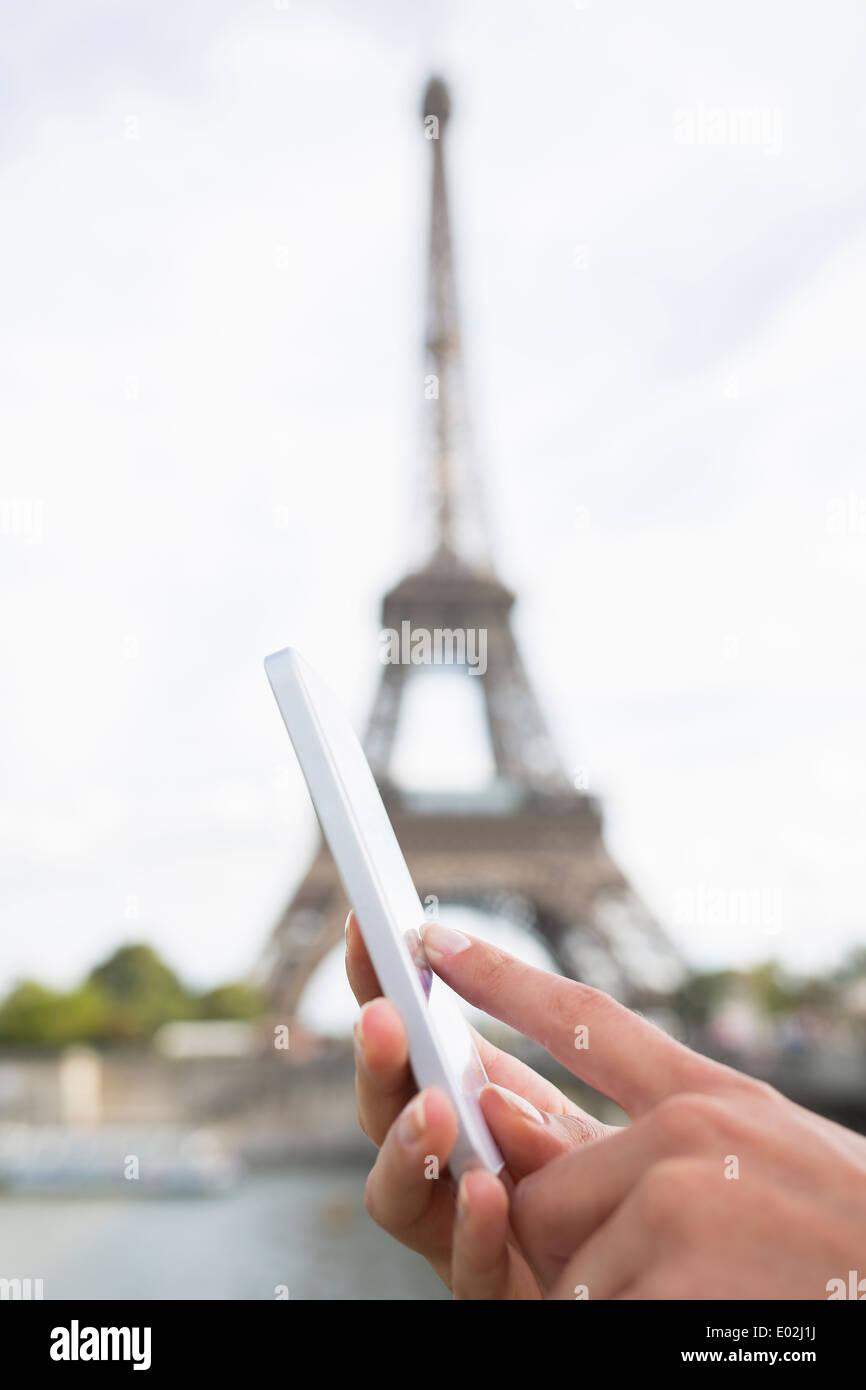 Close-up hand Female mobile phone Paris seine bridge message sms e-mail - Stock Image