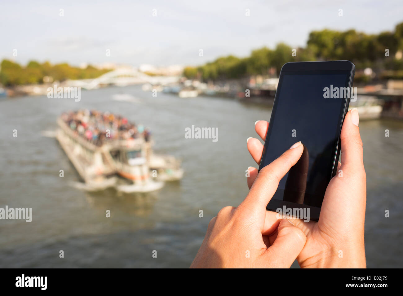 Close up of hands Female mobile phone houseboat seine bridge message sms e-mail - Stock Image