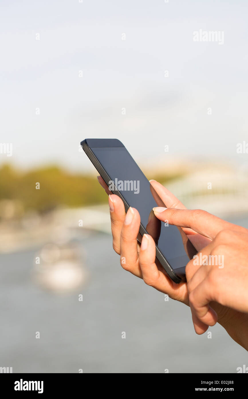 Female Close up of hands mobile phone houseboat seine bridge message sms e-mail - Stock Image