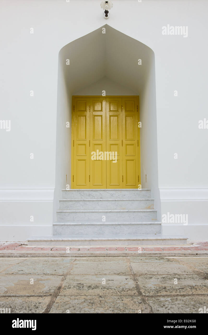 A beautiful yellow door with small steps below. A cement grid floor is in the foreground. Taken at a Thai Temple, Thailand. - Stock Image
