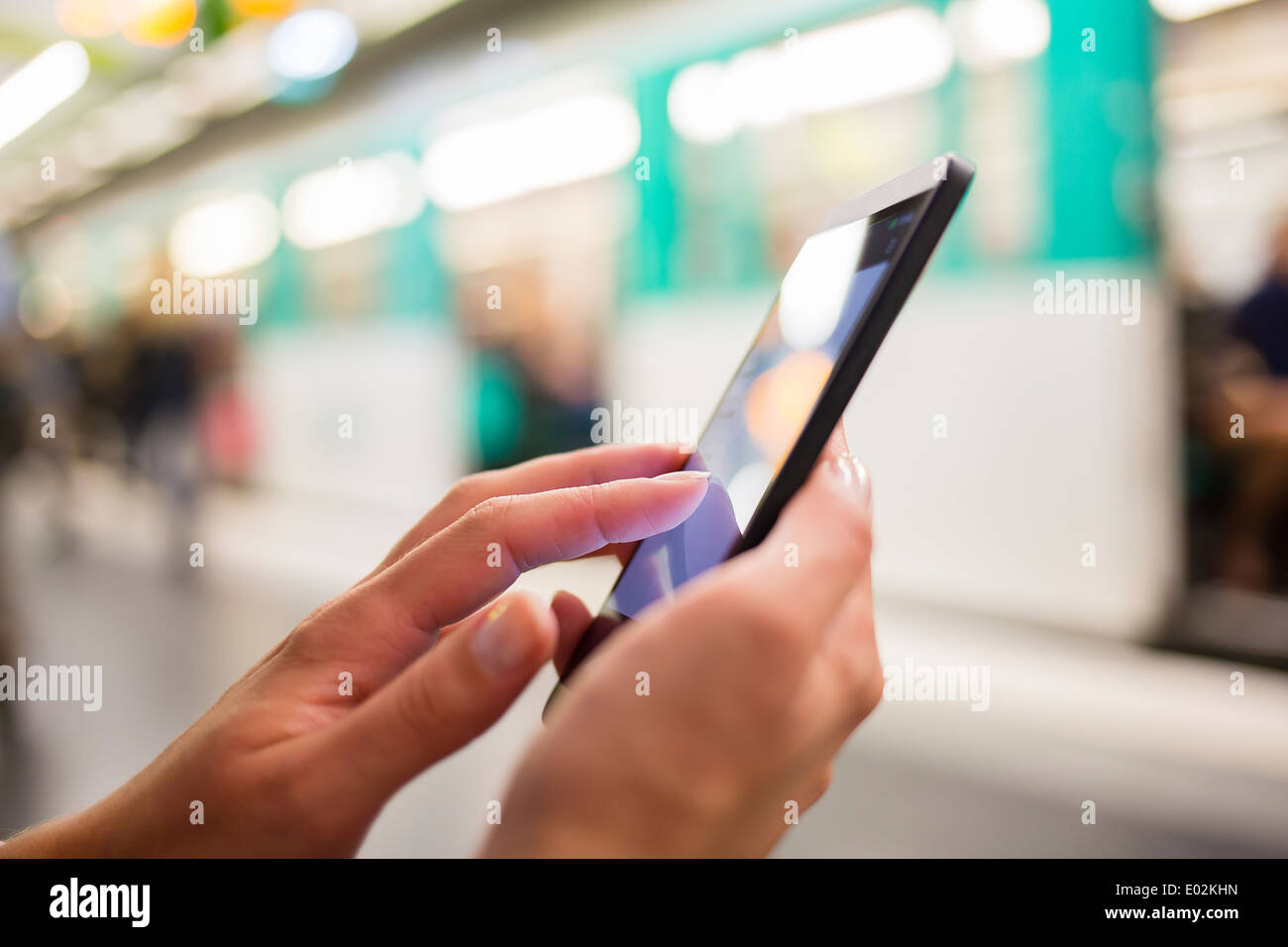 Female smartphone hand underground message sms e-mail - Stock Image