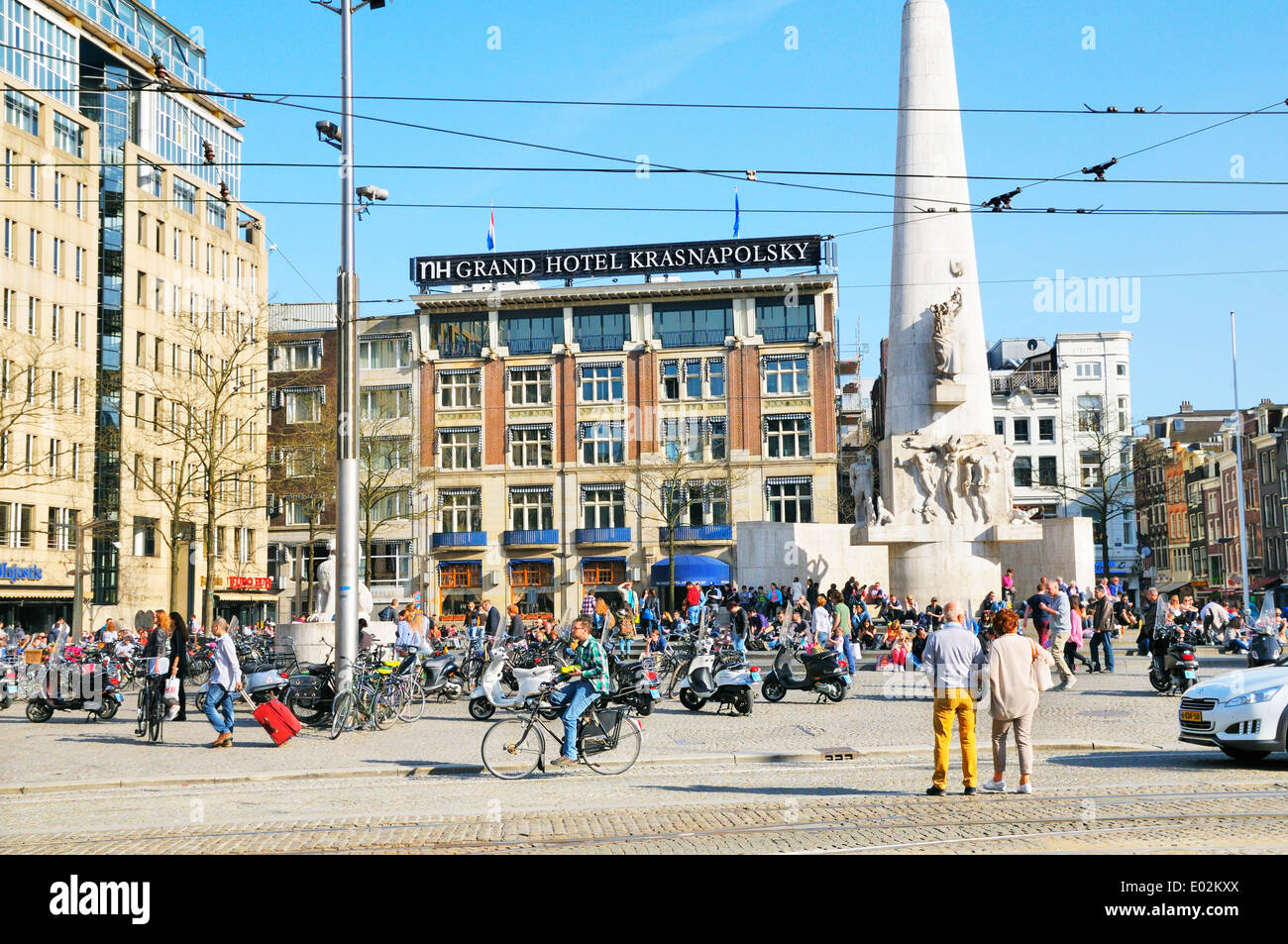 People relaxing in Dam Square outside NH Grand Hotel Krasnapolsky, Amsterdam, Netherlands - Stock Image