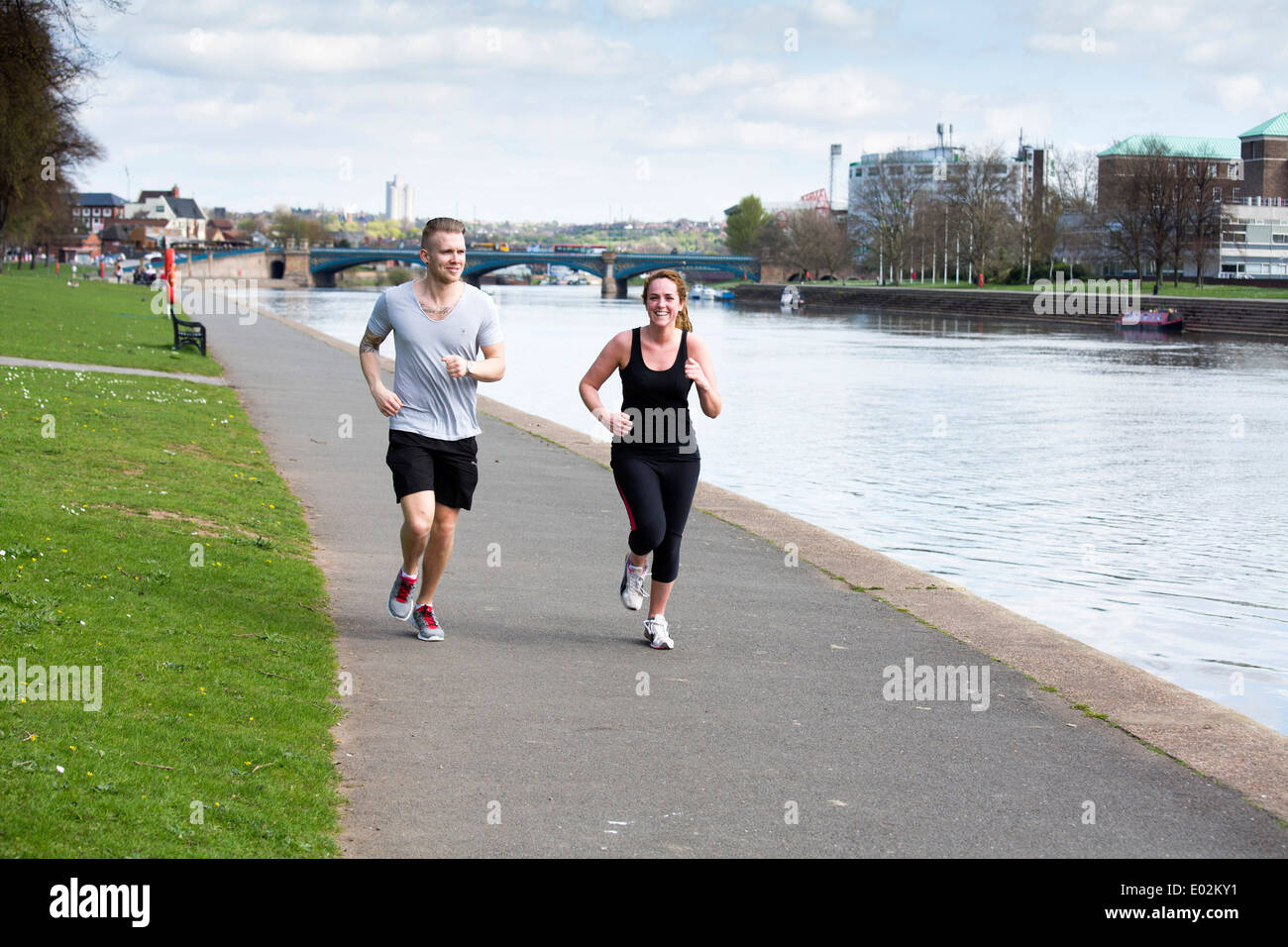 Two joggers running along the Embankment next to the River Trent in Nottingham. - Stock Image