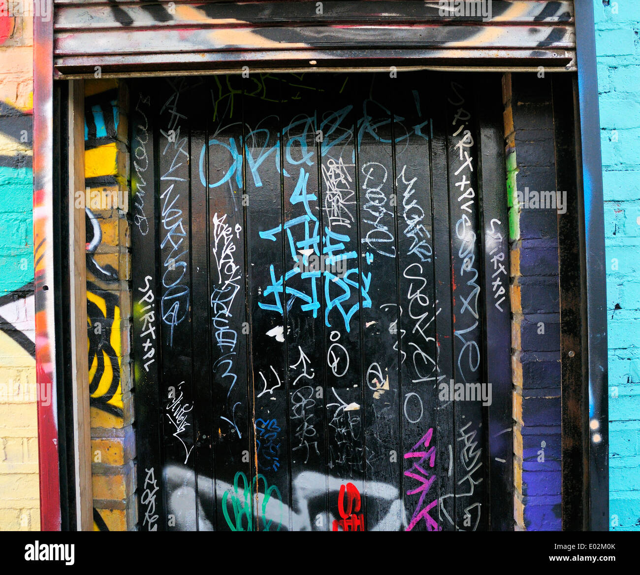 Graffiti tags on black door - Stock Image