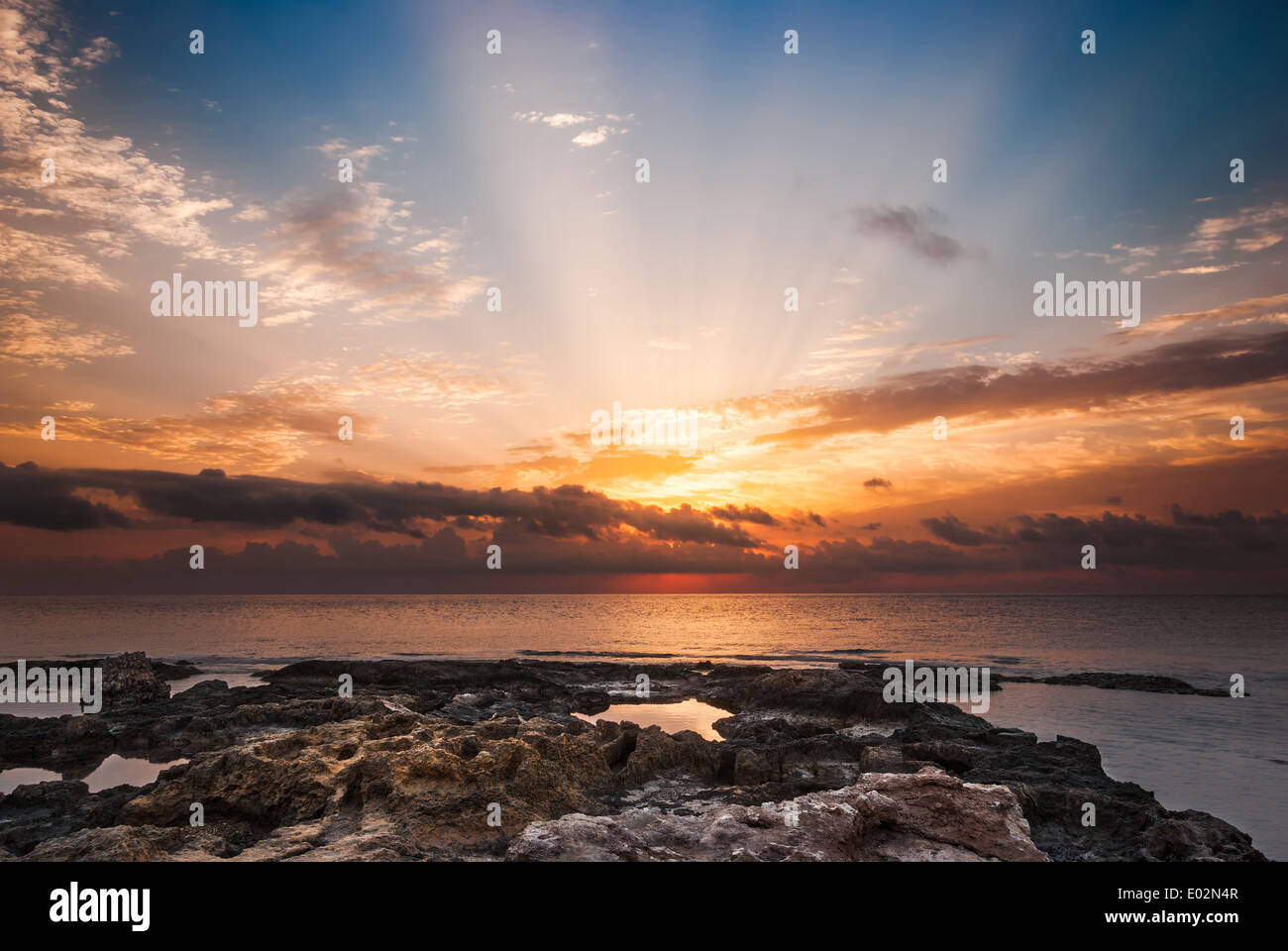 Rocky Beach and Sky with Sunrays on Cloudy Morning - Stock Image