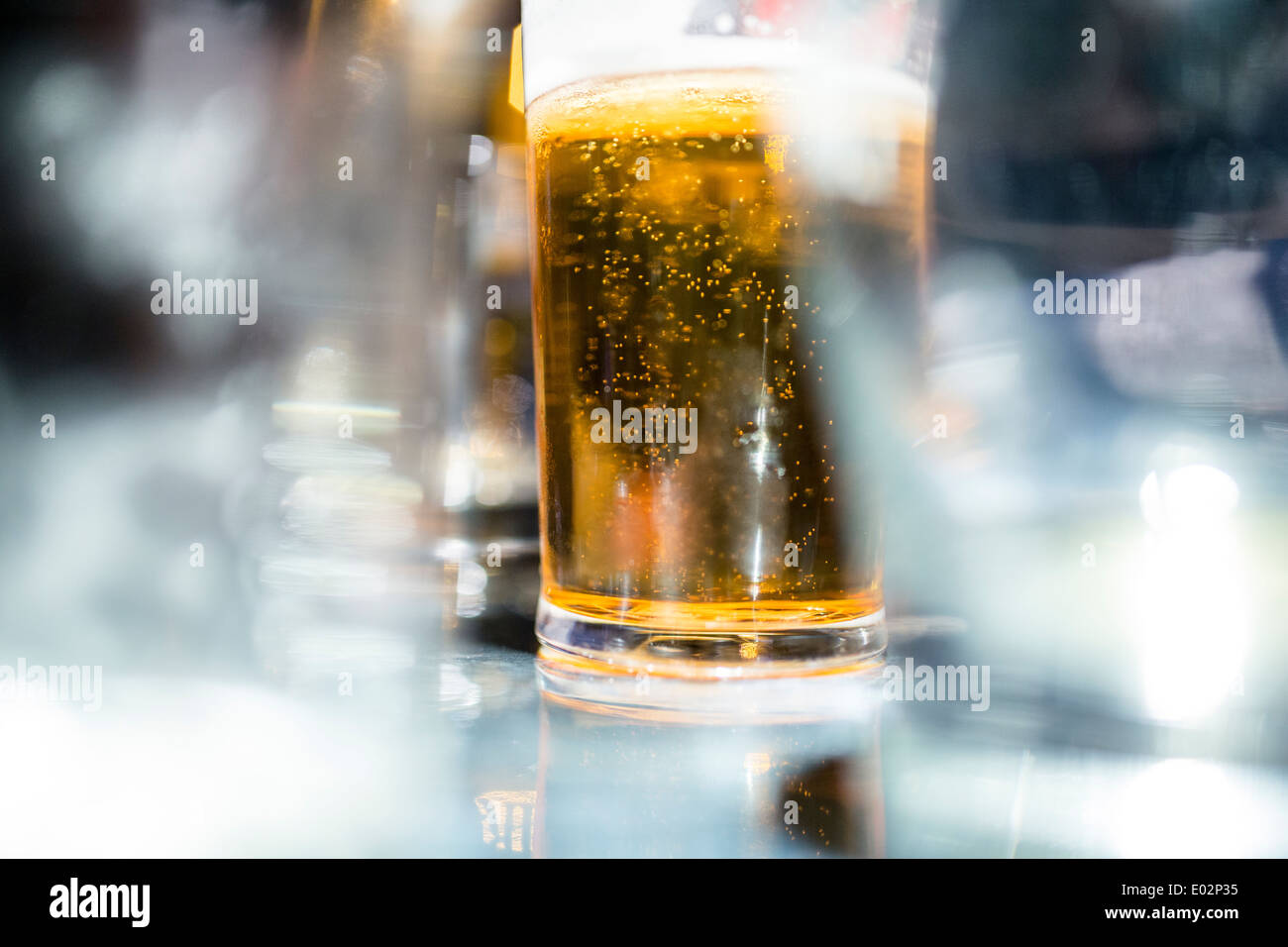 A pint of beer in a bar - Stock Image