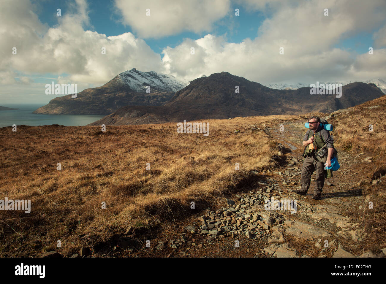 A hillwalker hikes a trail towards the Black Cuillin mountain range on the Island of Skye,Scotland - Stock Image