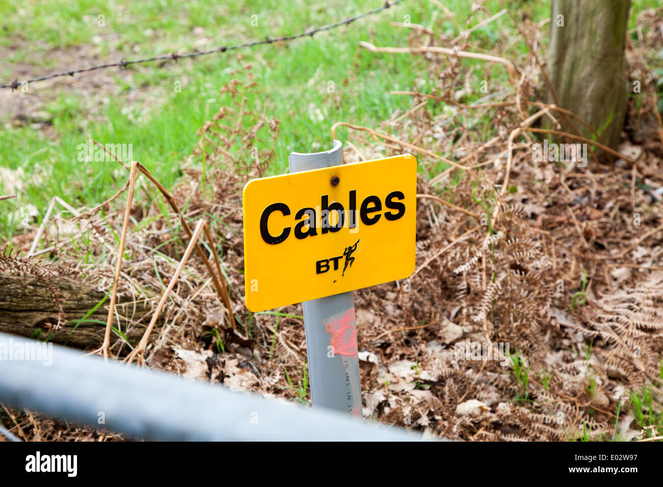 A bt or British Telecommunications sign warning that there are buried cables - Stock Image