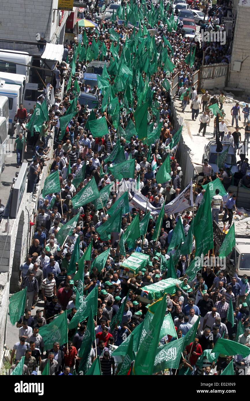 Ramallah, West Bank, Palestinian Territory. 26th Jan, 2009. Palestinian mourners wave the green flag of the Islamist movement Hamas as they attend the funeral of two Hamas members, Adel and Imad Awadallah, killed in 1998, after Israel returned the remains of four Palestinians to their families to their families, on April 30, 2014 in the West Bank city of Ramallah © Issam Rimawi/APA Images/ZUMAPRESS.com/Alamy Live News - Stock Image