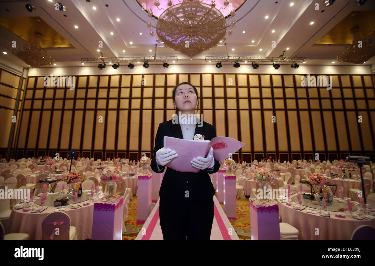 (140430) -- BEIJING, April 30, 2014 (Xinhua) -- Liu Ningbo checks a wedding ceremony scene less than two hours ahead of the event at a hotel in Changsha, capital of central China's Hunan Province, April 19, 2014. What is labor? What does labor mean, apart from the alteration of an object's position/status, the acquisition of financial rewards, and an exchange-based relationship? In this labor day special, our photographers will present three stories with distinctive protagonists: a coal mine worker, a wedding planner and an express courier. The meaning of labor will be told from their own wo - Stock Image