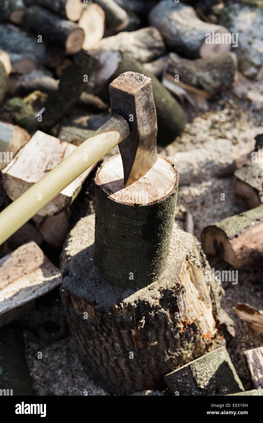 A woodpile a stack of logs and an axe wedged in a log. - Stock Image
