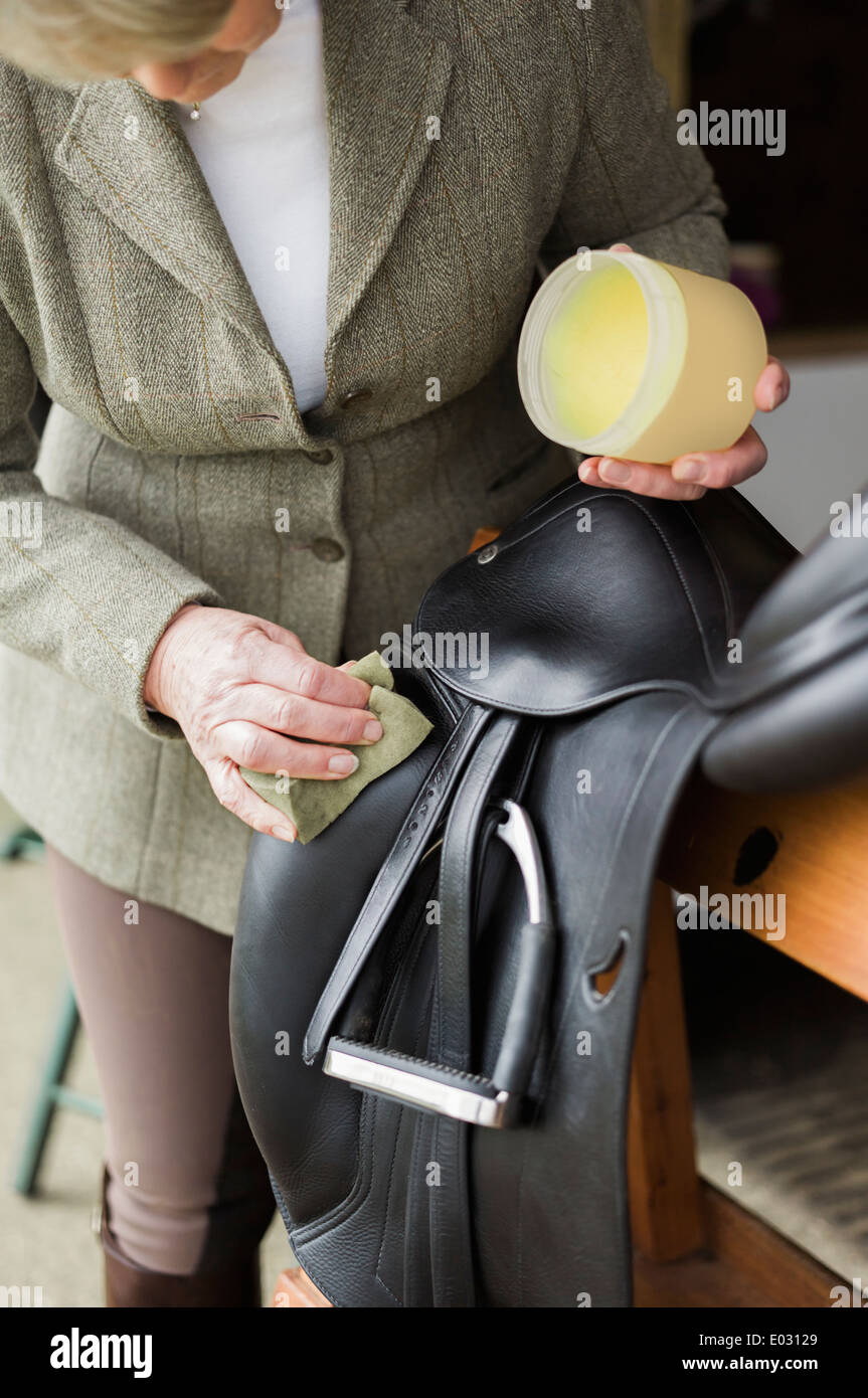A woman cleaning and preparing tack and saddle in the courtyard of a riding stable. - Stock Image