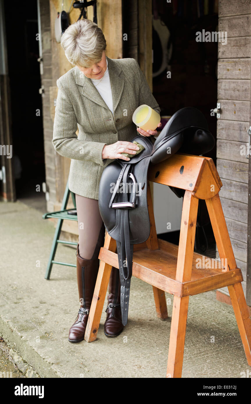 A woman cleaning and preparing tack and saddle in the courtyard of a riding stable. Stock Photo