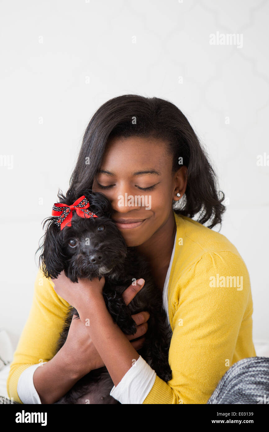 A young girl cuddling her small black pet dog. - Stock Image