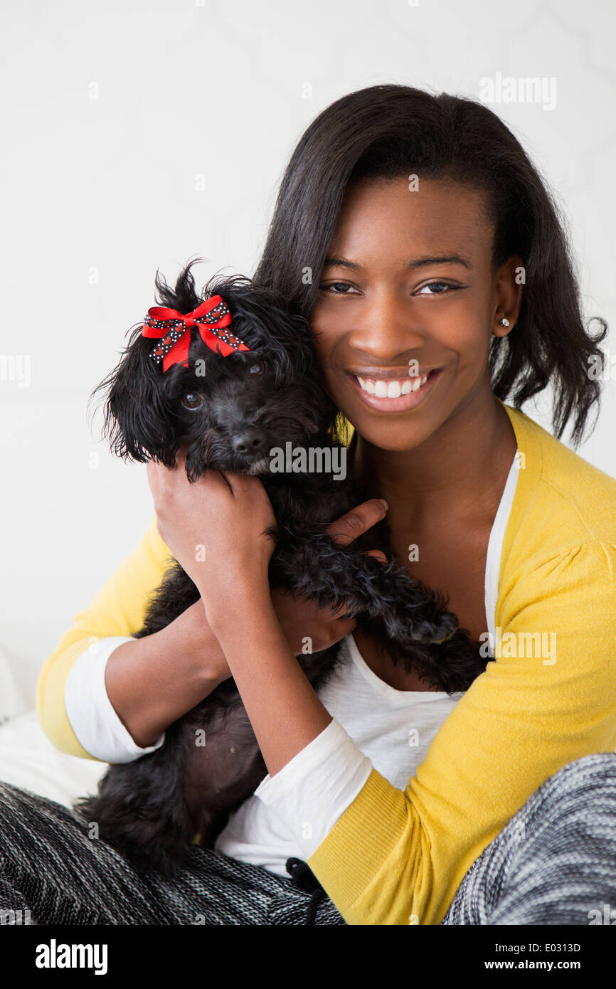 A young girl smiling holding her small black pet dog. - Stock Image