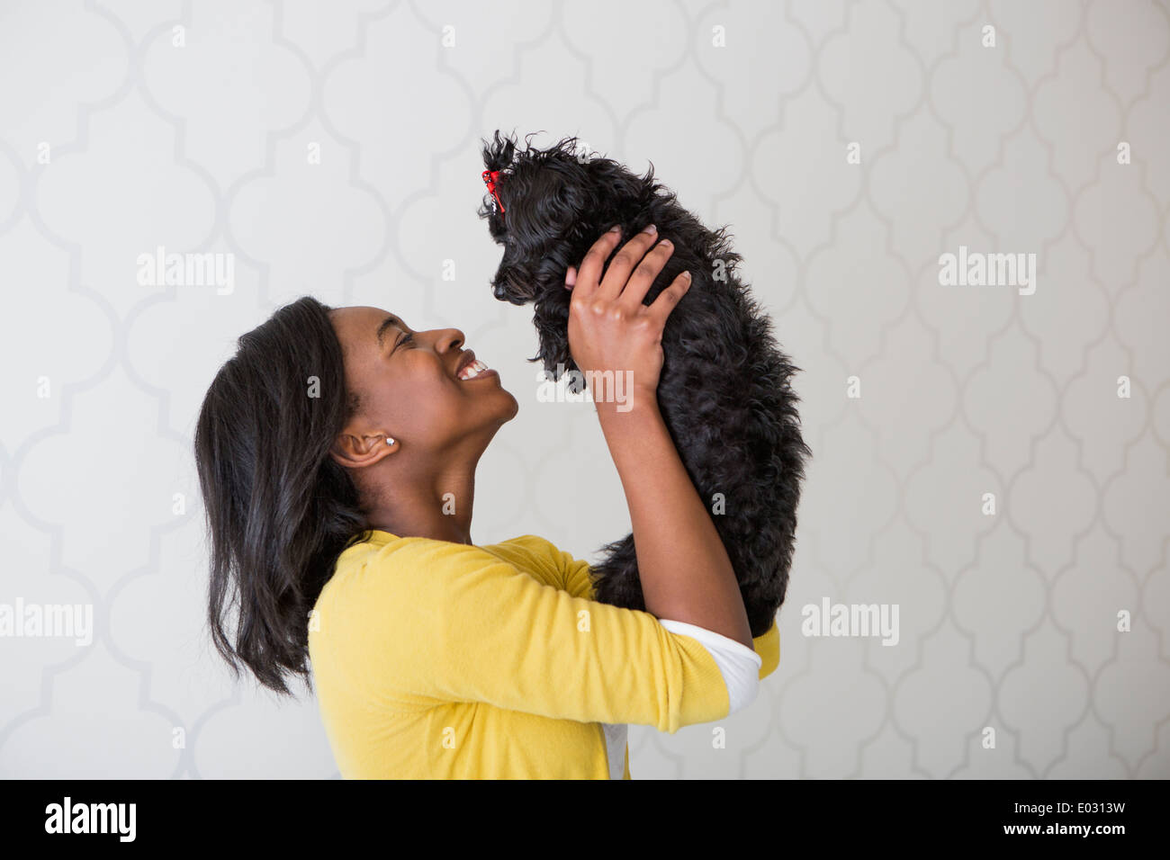 A young girl holding her small black pet dog. - Stock Image