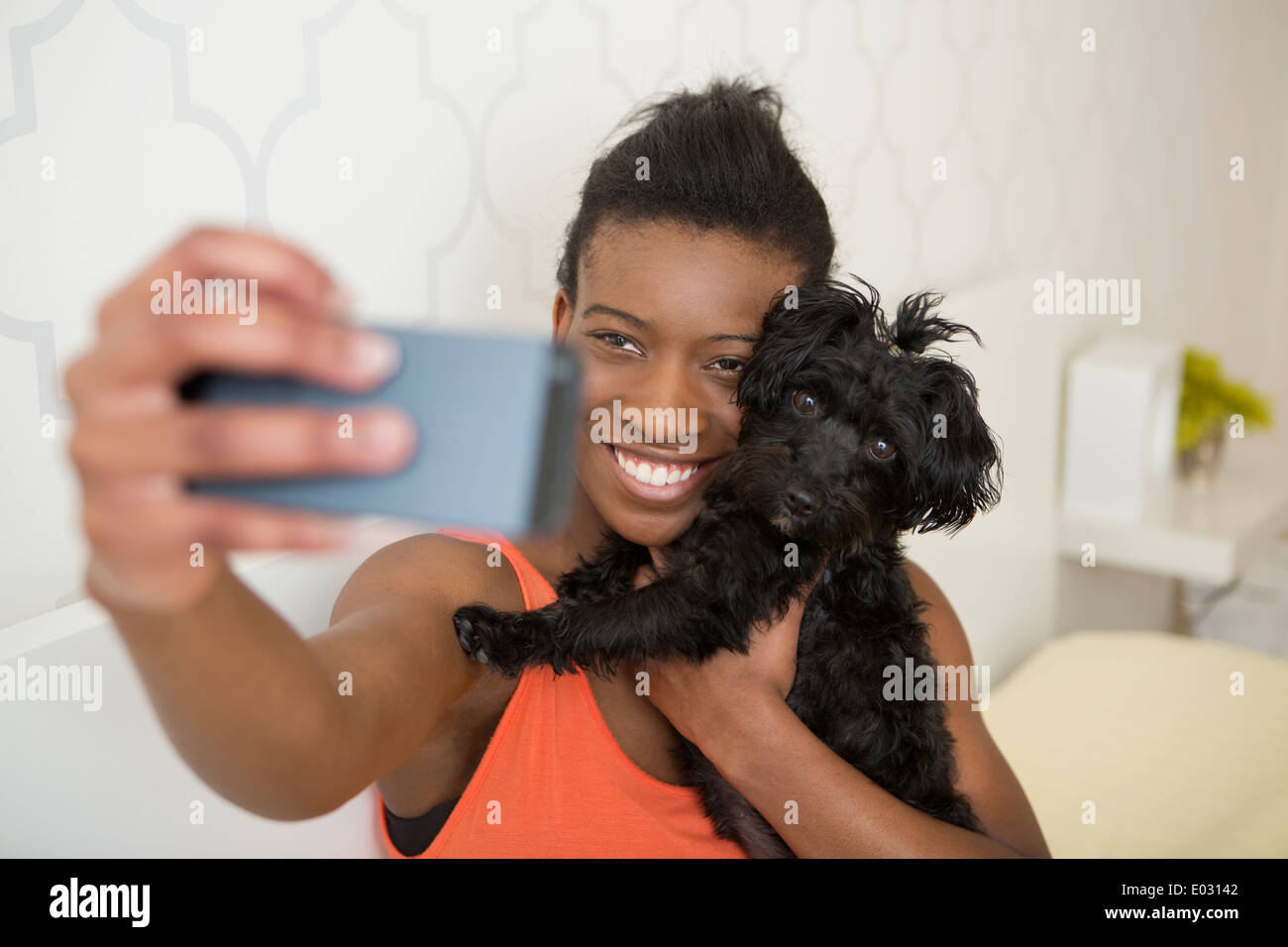 A young girl taking a selfy of her small pet dog and herself. - Stock Image