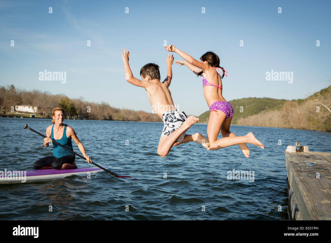 Two children leaping into the water from a jetty. Stock Photo