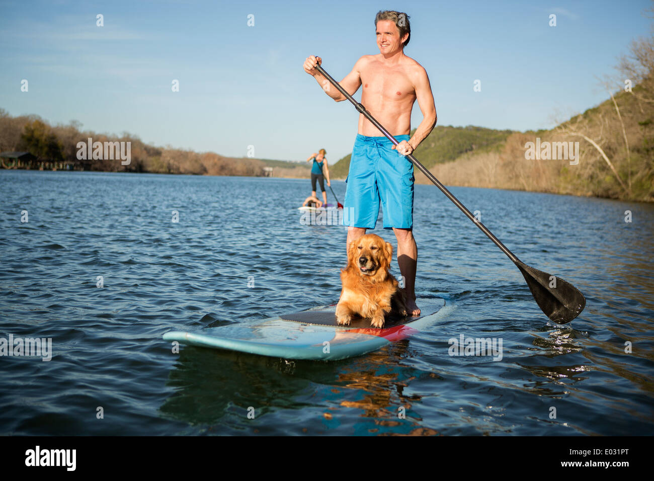 A man standing on a paddleboard with a dog. - Stock Image