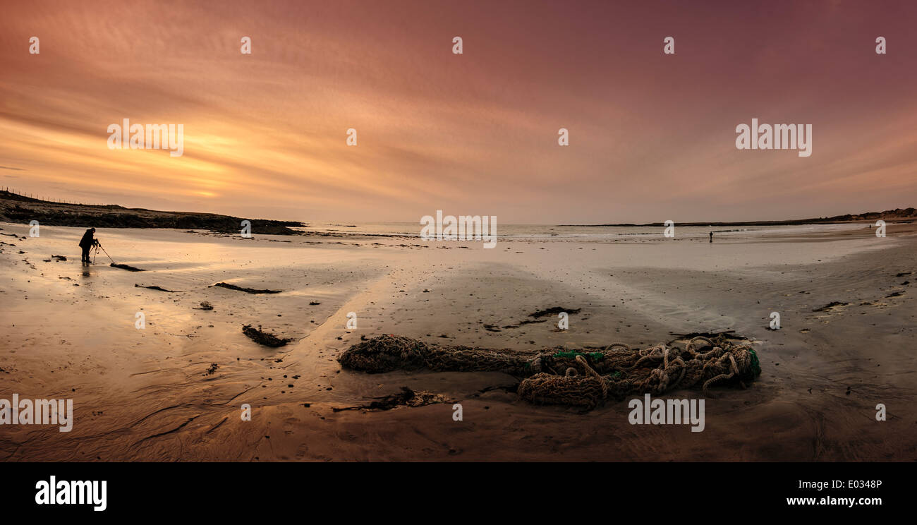 A photographer records the sunset on the beach at Balivanich, Benbecula, Outer Hebrides, Scotland - Stock Image