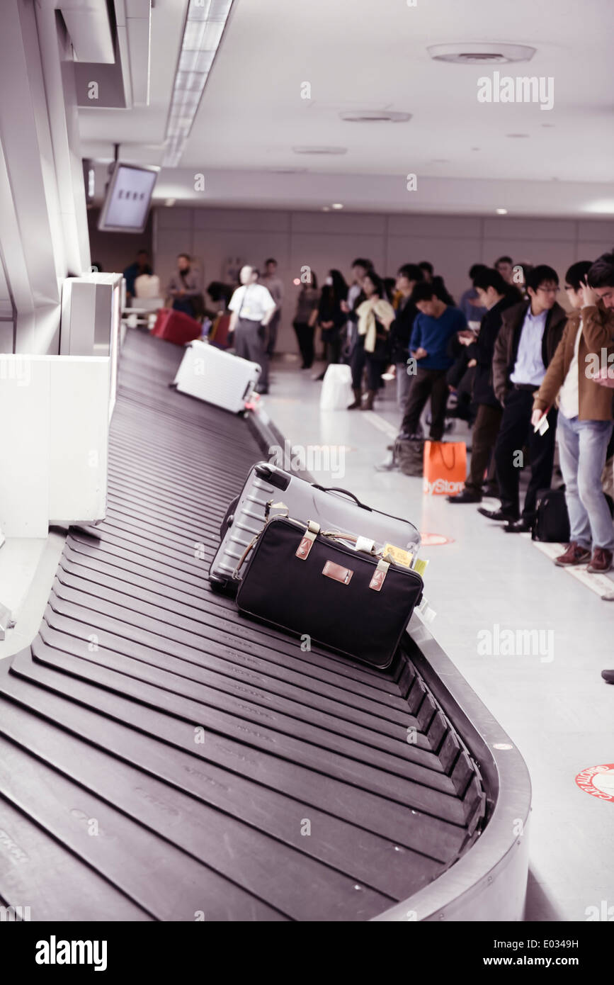 People waiting for their luggage at Narita International airport baggage claim conveyor carousel, Japan - Stock Image