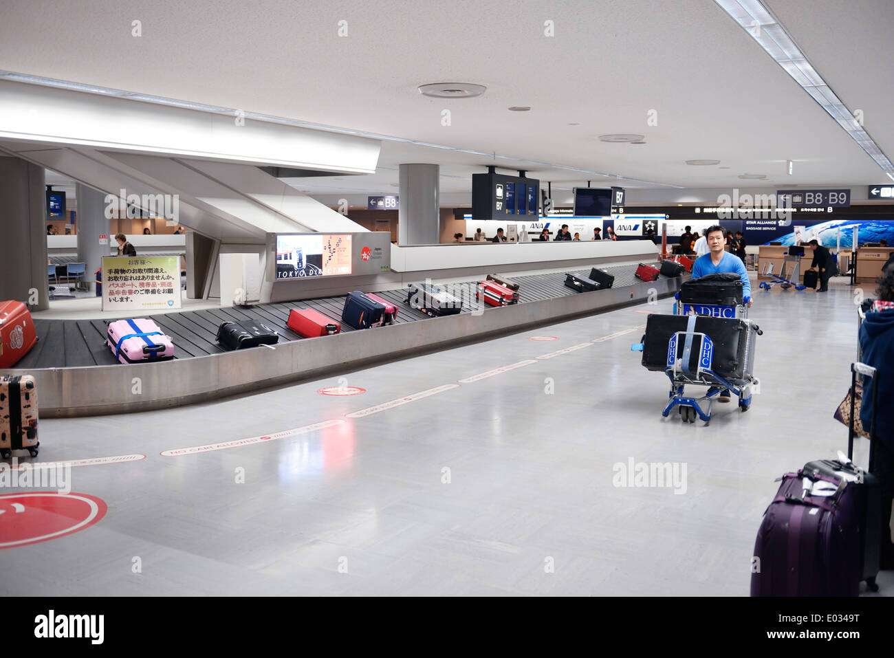 People claiming luggage at Narita International airport baggage conveyor carousel, Japan - Stock Image