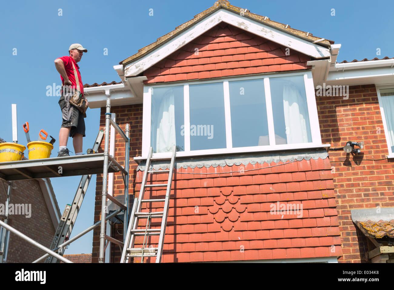 Tradesman Fitting New Fascia to House - Stock Image