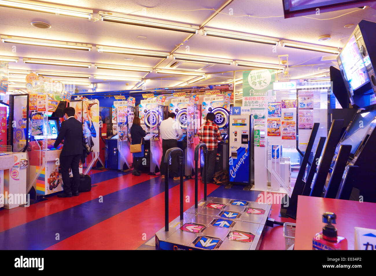 People playing slot machines at an arcade in Tokyo, Japan - Stock Image