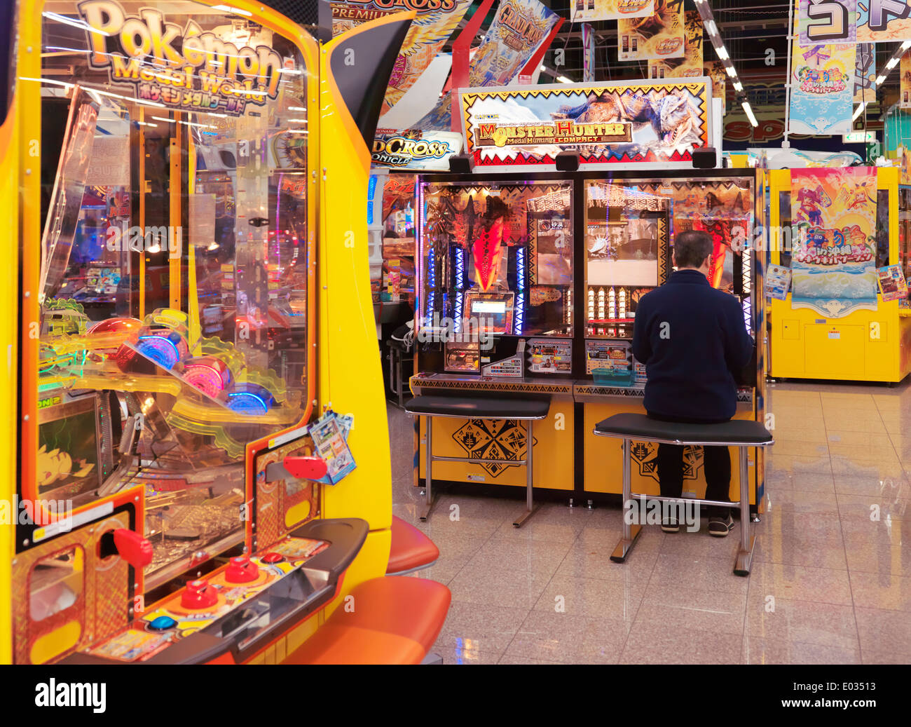 Person playing Monster Hunter arcade slot machine in Odaiba, Tokyo, Japan - Stock Image