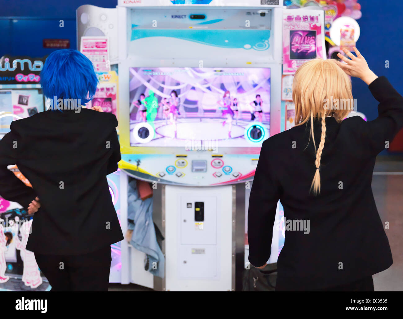 Girls playing dance station slot machine at arcade in Odaiba, Tokyo, Japan - Stock Image