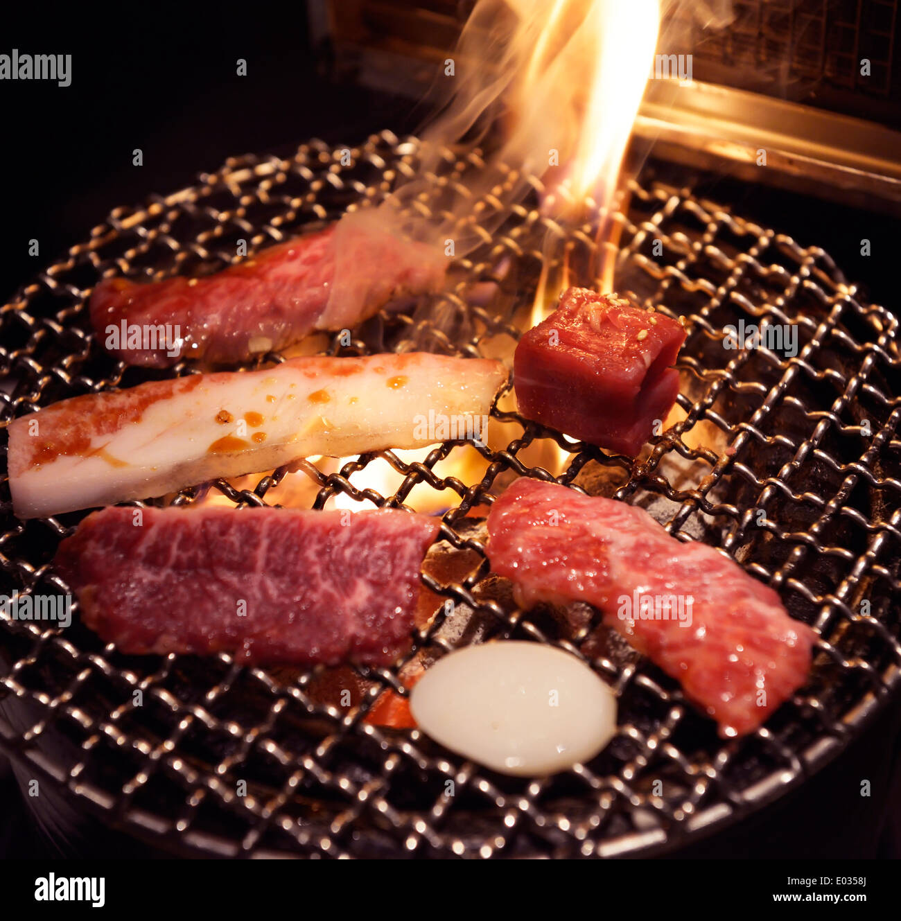 Meat On Grill Being Cooked On Fire At A Japanese Grill Restaurant Stock Photo Alamy